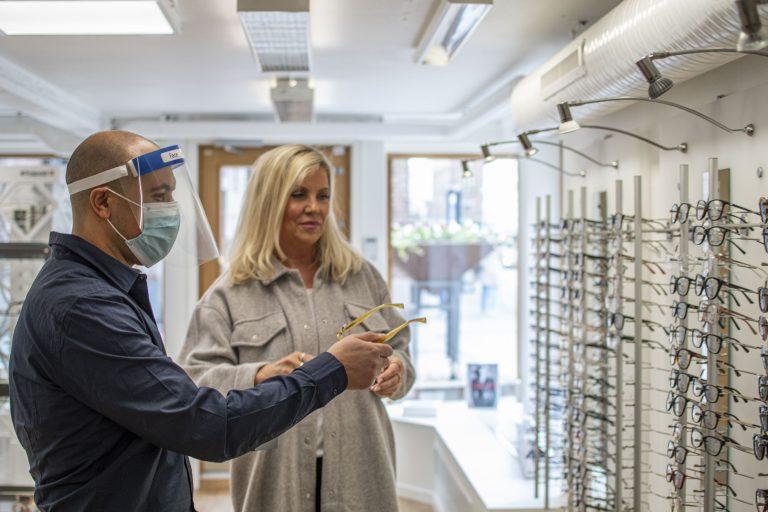 Optiker visar kund glasögon i Svensk optikhälsas butik i Borås.